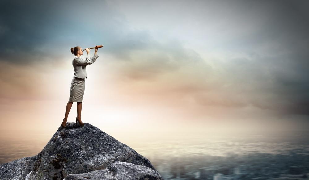 Image of businesswoman looking in telescope standing atop of rock.jpeg